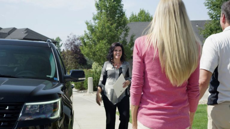 Alie walking by black car to meet new friends by door
