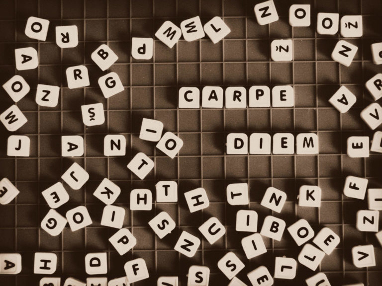 scrabble on a grid spelling out carpe diem at a game cafe
