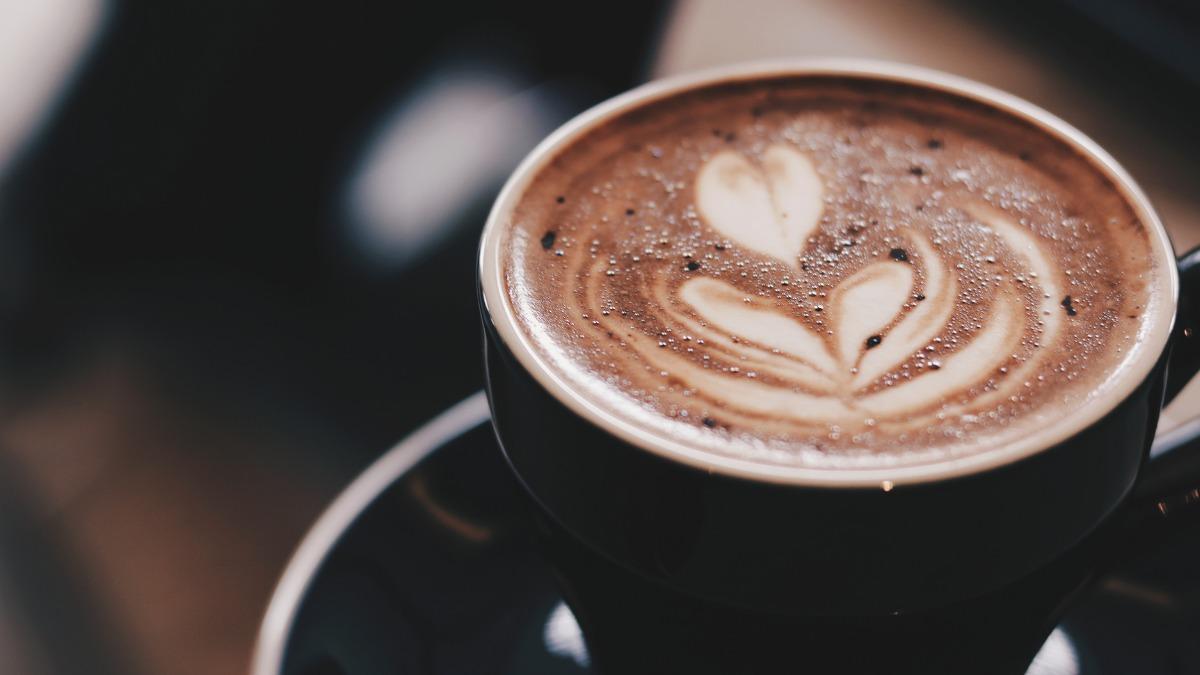 latte art in black coffee mug